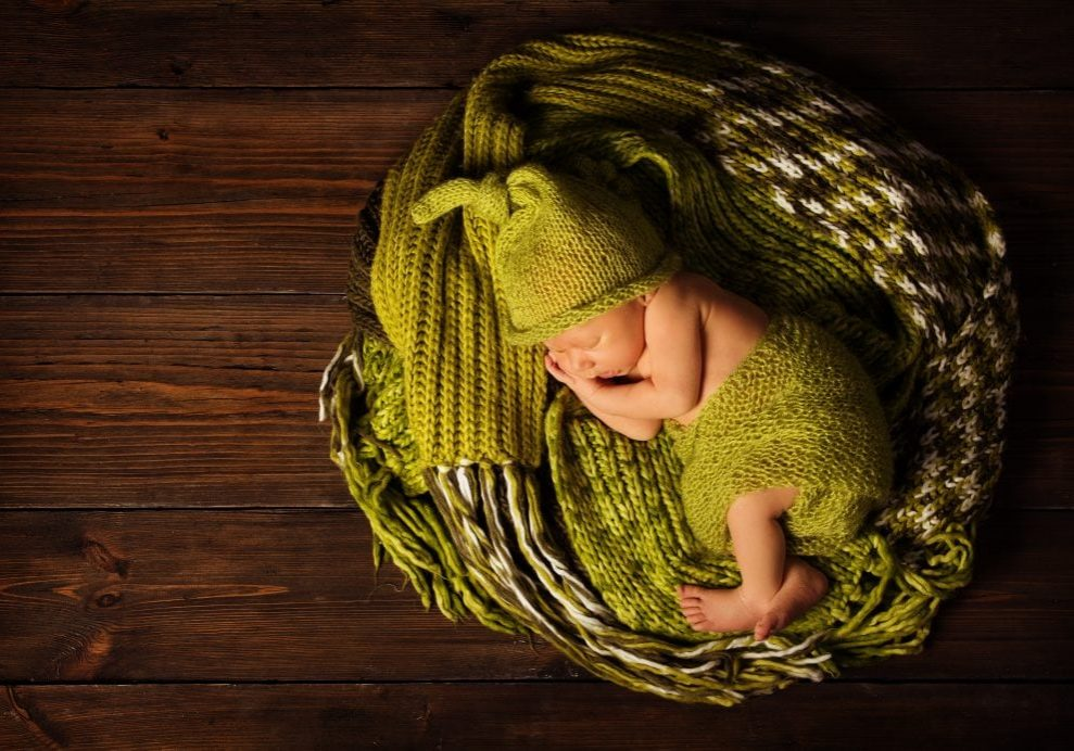 baby newborn portrait, kid sleeping in woolen hat on brown wooden background